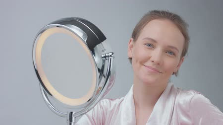 vanity : smiling young woman looks at camera and smiling and then looking at herself in mirror