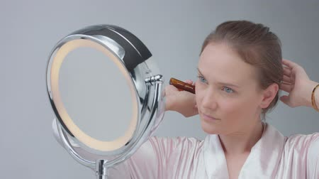 vanity : young blue eyed caucasian woman looking at mirror and combing her hair
