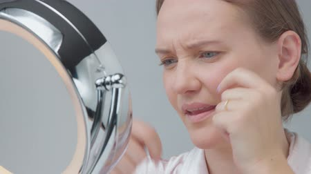 yaşlanma : unhappy disappointed woman looking at mirror and found a pimple, trying to squieeze it, Skin imperfection video Stok Video