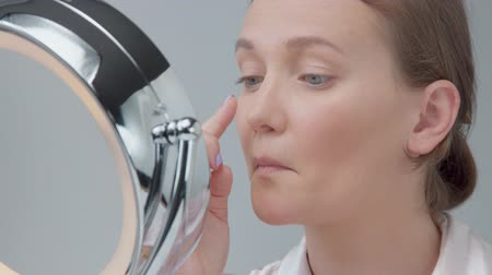 marnost : young woman sad about her skin looking at beauty mirror