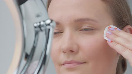 lotion : woman using a cotton pad under eyes zone