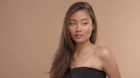 neutro : panned video portrait of thai asian model in studio with ideal strobing skin and straighr hair. Slow motio from 60fps