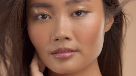 neutro : closeup thai asian model with ideal glowing strobing skin turning and watching aside and to the camera