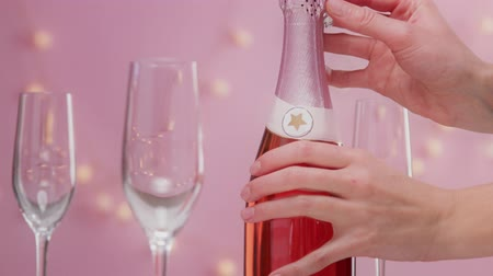 vibes : Pink sparkling wine with womans hand and glasses on pink background with christmas lights female christmas celebration woman hand open the bottle of rose champagne