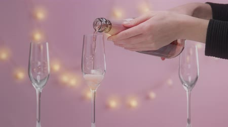 vibes : Pink sparkling wine with womans hand and glasses on pink background with christmas lights female christmas celebration slow motion woman hand full glass with pink champagne. Stock Footage