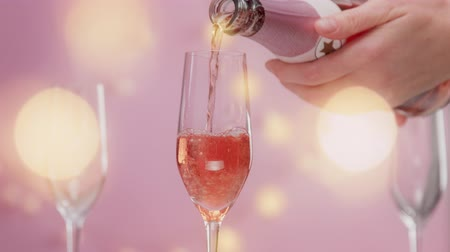 vibes : Pink sparkling wine with womans hand and glasses on pink background with christmas lightsslow motion woman hand full glass with rose sparkling wine and lights behind the camera.