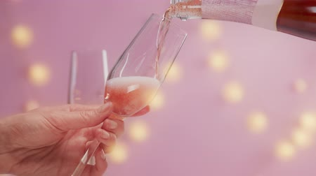 vibes : closeup slow motion woman serve a glass of pink rose sparkling wine