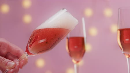 szampan : Pink sparkling wine with womans hand and glasses on pink background with christmas lights closeup how rose sparkling wine goes out of glass