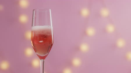 vibes : slow motion of cherry falling in glass of rose pink champagne