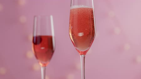 szampan : closeup slow motion serving pink rose sparkling wine and cherry falling in it then Wideo