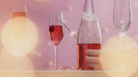 vibes : composition of glasses and bottle of rose champagne and womans hand holding bengal light Stock Footage