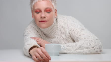 neutro : blonde woman with short haircut wears knitted sweater lying on the table thenlift up and take a cup of hot drink