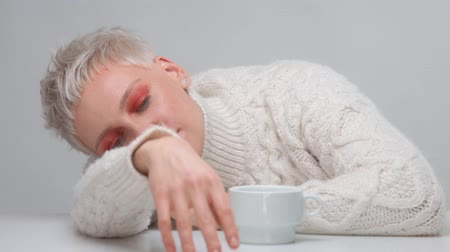 neutro : blonde woman with short haircut in white knitted sweater with a white cup of hot drink lying on the table. Watching aside and dreaming Vídeos