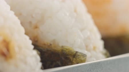 pickled : macro panned video of three onigiri rice ball texture. Japanece food in bento Stock Footage