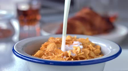 senki : closeup slowmotion cornflakes fallin in bowl and milk then pouring on it