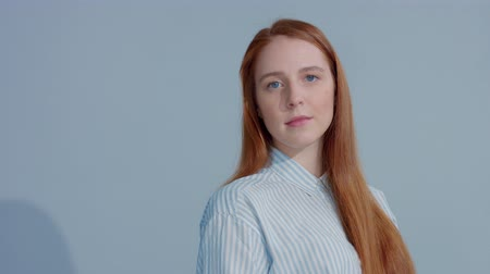идеальный : gingerhead red hair model turning to the camera on blue background. BEauty shiny stright red ginger hair Стоковые видеозаписи