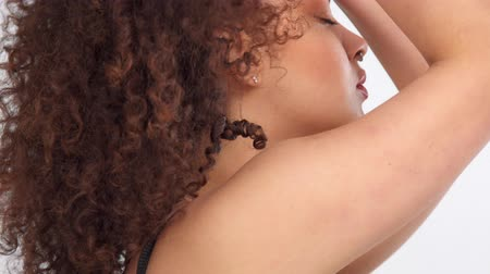 sorriso largo : closeup portrait of mixed race model with freckles touching her hair and turning to a camera and smiling