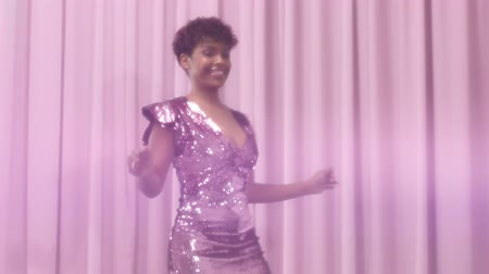 disko : black mixed race woman with short haircut and curly natural hair wears sequin sparkly dress in pink pass from the left to the right dancing Stok Video