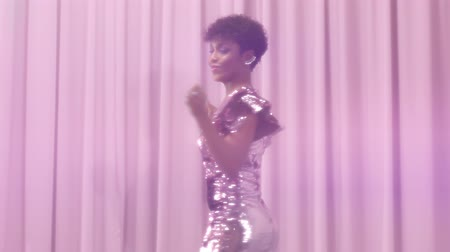 femenine : black mixed race woman with short haircut and curly natural hair wears sequin sparkly dress in pink pass throught frame from left to the right dancing and rolling in slow motion from 60 fps Stock Footage