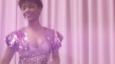 femenine : black mixed race woman with short haircut and curly natural hair wears sequin sparkly dress in pink. Tlit camer lift up showing dancing woman in sparkly dress. Stock Footage