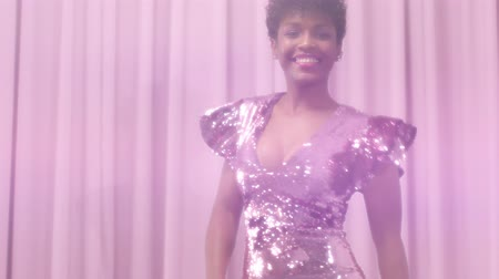 femenine : black mixed race woman with short haircut and curly natural hair wears sequin sparkly dress in pink. Dancing womn and sparkly sequin dress makes lens flair