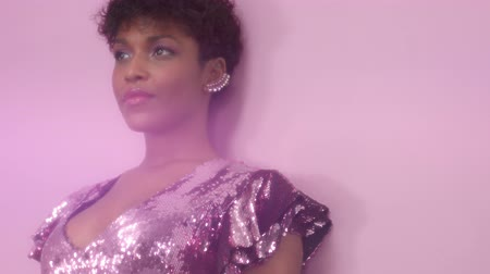 femenine : black mixed race woman with short haircut and curly natural hair wears sequin sparkly dress in pink . Tilt camera movement. Portrait of smiling black woman