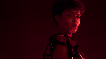 femenine : closeup portrait of mixed race african american woman with short hair in night club in red light turning to the camera and light reflect to her cheek from sparkly dress