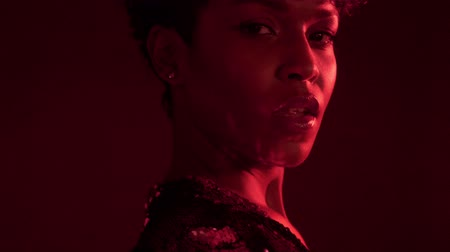 femenine : closeup portrait of mixed race african american woman with short hair in night club in red light turning to the camera and light reflect to her cheek from sparkly dress. tilt camera movement Stock Footage