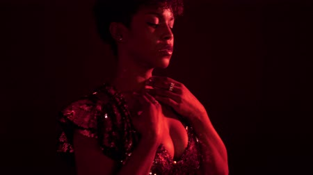 femenine : mixed race black woman dancing in night club in red light. Wears sparkly sequin dress