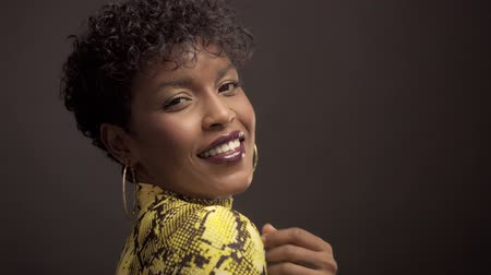 femenine : mixed race african american woman in bright yellow dress with python print. 90s style touches her natural curly short hair and smiling to the camera. Studio shoot black background Stock Footage