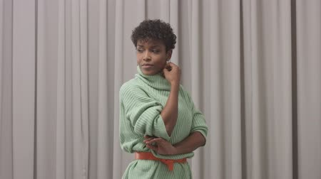 femenine : woman in mint sweater in studio with grey curtain background, 90s offise style poses to a camera