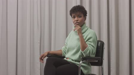 femenine : woman in mint sweater in studio with grey curtain background, 90s offise style sit on the chair and looking to the camera. pan camera movement Stock Footage
