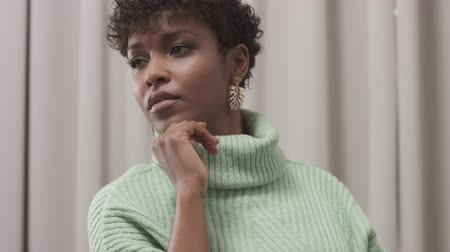 femenine : woman in mint sweater in studio with grey curtain background, 90s offise style Slow motion closeup dolly portrait of african american woman