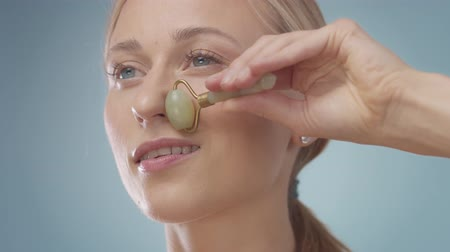 kuvars : Closeup of blonde model using a quartz facial roller under eye zone massage. Lifting undereye massage with stone rollers. Stok Video