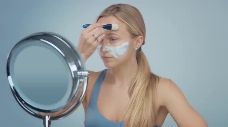 маслянистый : young blond model cover her face with blue clay cleansing mask