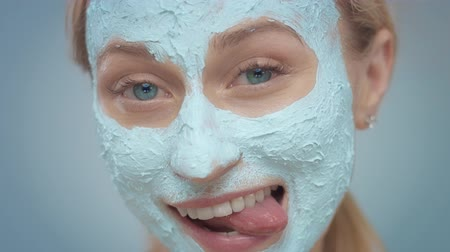 olajos : happy smiling blue eyed model with blue clay facial mask cover her face. Have fun showing tongueand smiling wide