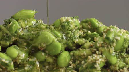 bamboo steamer : mix of edamame with sesame seeds and avocado and olive oil pouring on it. Green veggie food concept. Closeup edamame mix Stock Footage