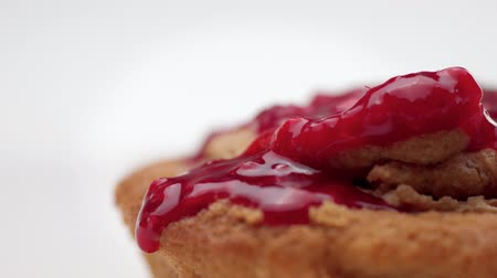 tartlet : macro of red fruit topping pouring on dessert and drops falling Stock Footage