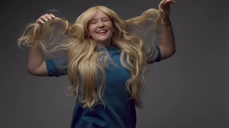 felnőtt : nordic blond model in studio with dramatic top lightumping and her ling curly hair spring Happy smiling laughing screaming Stock mozgókép
