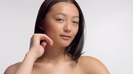 плечо : mixed race asian model in studio beauty shoot Model watching aside and then to the camera. Brown eyed model with ideal skin and natural makeup