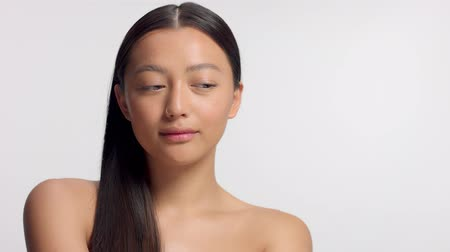 nomakeup : mixed race asian model in studio beauty shoot Model poses to a camera, straight hair combed to right side. Ideal skni and no makeup makeup Head and shoulders crop