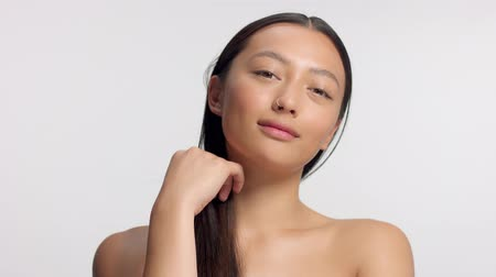 nomakeup : mixed race asian model in studio beauty shoot. Head and shoulders crop model touches her hair and watching to the camera Stock Footage