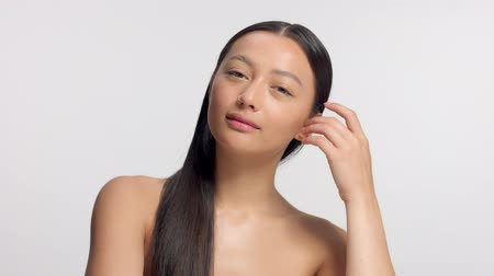 nomakeup : mixed race asian model in studio beauty shoot Fresh model with no makeup makeup watching to the camera amd touches her straight hair