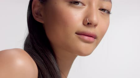 идеальный : mixed race asian model in studio beauty shoot Super oom closeup portrait of mixed race asian model poses to a camera in studio on white Стоковые видеозаписи