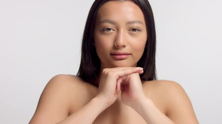 nomakeup : mixed race asian model in studio beauty shoot Tilt movement of camera model with head rest on hands watching straight to the camera Stock Footage