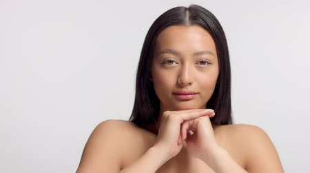 nomakeup : mixed race asian model in studio beauty shoot Panned video of model with head rest on her hand watching to the camera