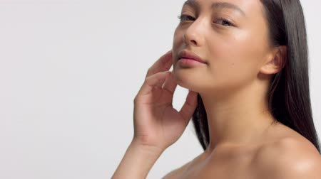 nomakeup : mixed race asian model in studio beauty shoot. Model touches her face skin and wathcing to the camera. Ideal skin