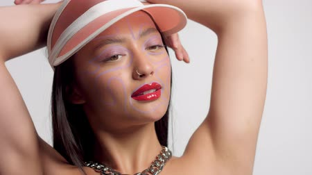 nomakeup : mixed race asian model in studio creative art makeup with hands up poses to a camera Stock Footage