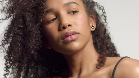 model s : closeup portrait s of young mixed race model with curly hair in studio with natural neutral makeup and glowin skin