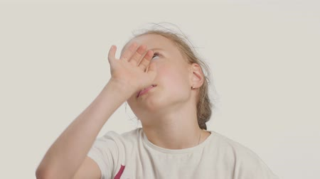 facepalm : young girl makes facepalm alone in studio on white